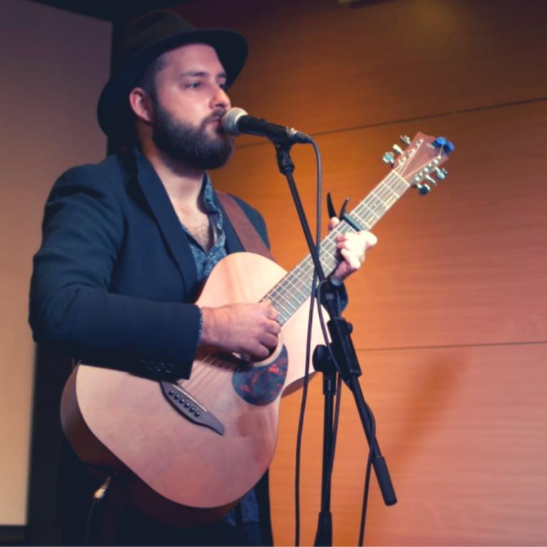 Wykonawca w kapeluszu i z gitara podczas wystepu
