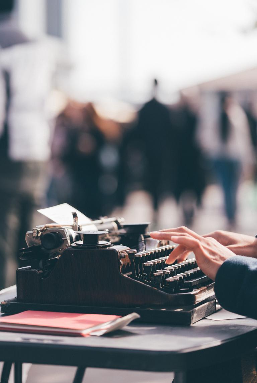 Maszyna do pisania a na niej kobiece dłonie