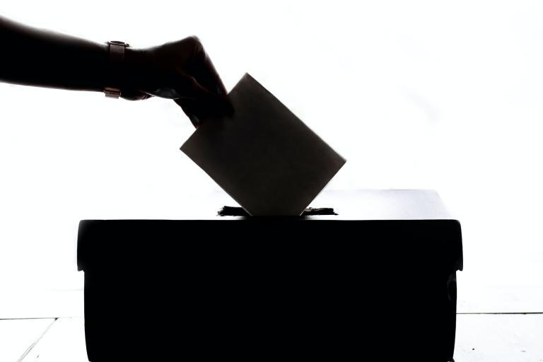 Ręka wkładająca swój głos do urny wyborczej.