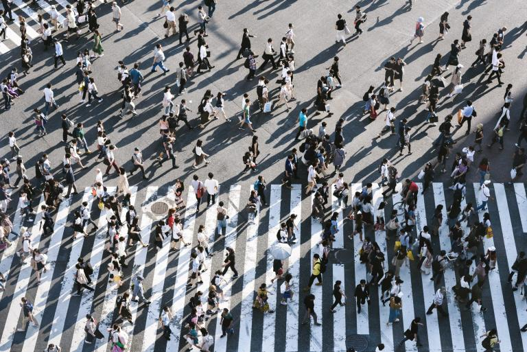 Tłum ludzi przechodzący przez pasy na jezdni